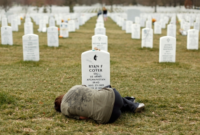 Lesleigh Coyer, 25, of Saginaw, Michigan, lies down in front of the grave of her brother, Ryan Coyer, who served with the U.S. Army in both Iraq and Afghanistan, at Arlington National. www.euronews.com